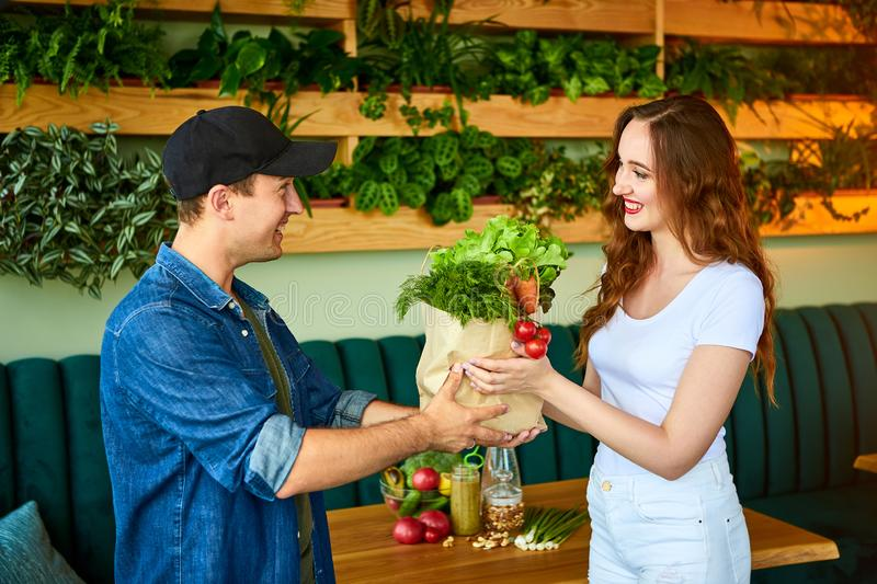 Courier service worker delivering fresh food, giving shopping bag to a happy woman client on the kitchen at home. Online grocery stock photos