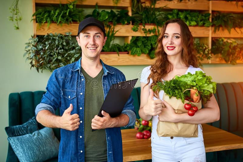 Courier service worker delivering fresh food, giving shopping bag to a happy woman client on the kitchen at home. Online grocery royalty free stock photography