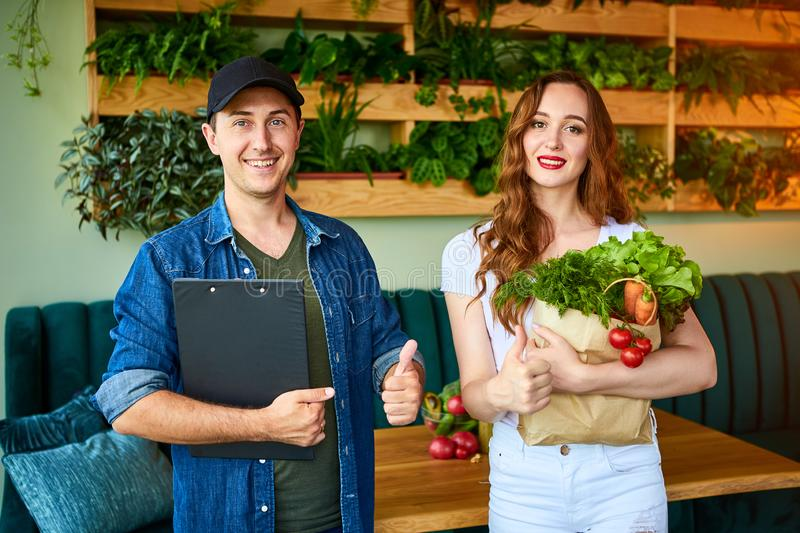 Courier service worker delivering fresh food, giving shopping bag to a happy woman client on the kitchen at home. Online grocery stock photo