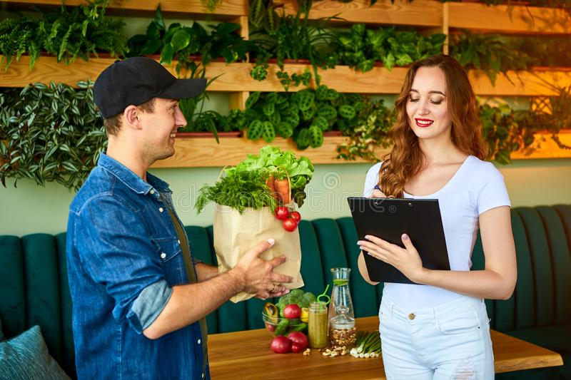 Courier service worker delivering fresh food to a happy woman client signing some documents on the kitchen at home. Online grocery stock photo