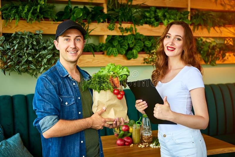 Courier service worker delivering fresh food to a happy woman client signing some documents on the kitchen at home. Online grocery royalty free stock images