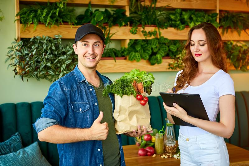 Courier service worker delivering fresh food to a happy woman client signing some documents on the kitchen at home. Online grocery stock photos
