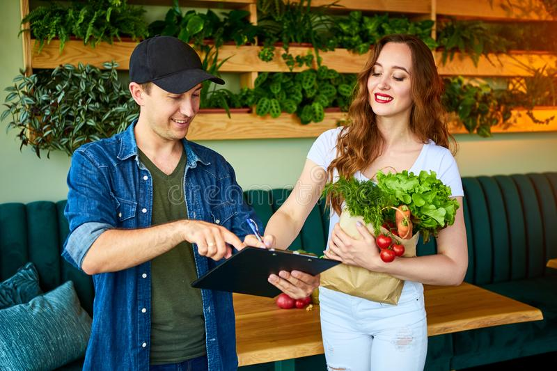 Courier service worker delivering fresh food to a happy woman client signing some documents on the kitchen at home. Online grocery stock photography