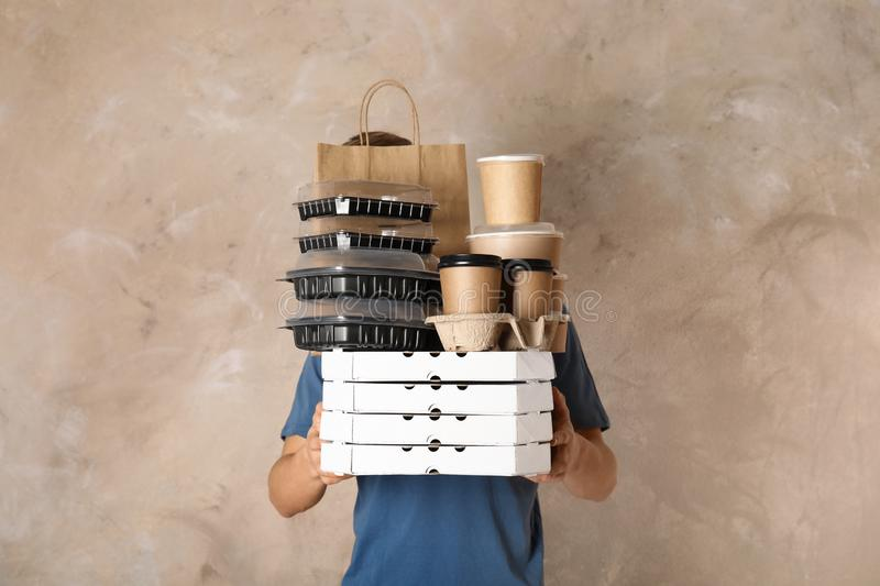 Courier with stack of orders on beige background. Food delivery service stock images