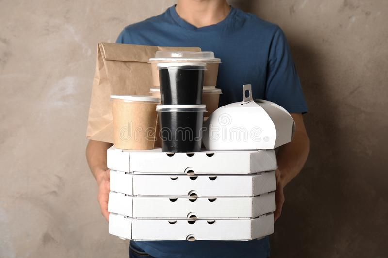 Courier with stack of orders on beige background. Food delivery service royalty free stock image