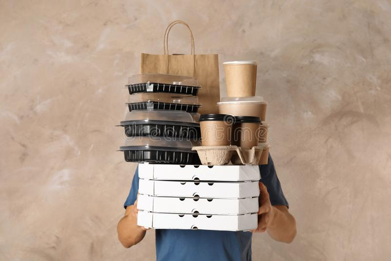 Courier with stack of orders on beige background. Food delivery service royalty free stock images