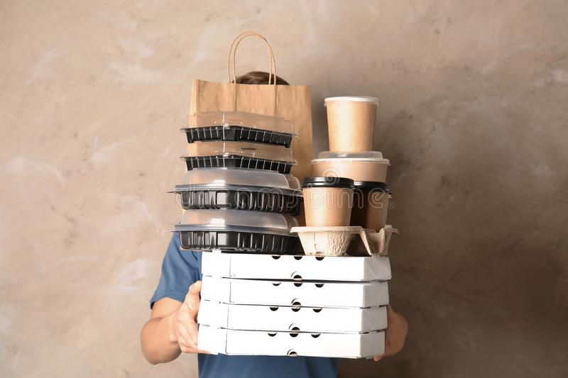 Courier with stack of orders on beige background. Food delivery service royalty free stock photography
