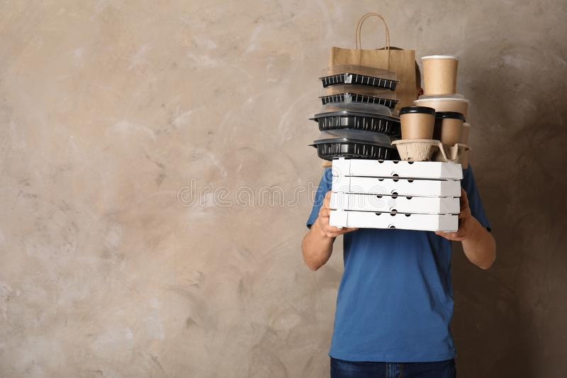Courier with stack of orders on beige, space for text. Food delivery service. Courier with stack of orders on beige background, space for text. Food delivery royalty free stock photography