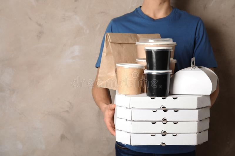 Courier with stack of orders on beige background. Food delivery service. Courier with stack of orders on beige background, space for text. Food delivery service royalty free stock images