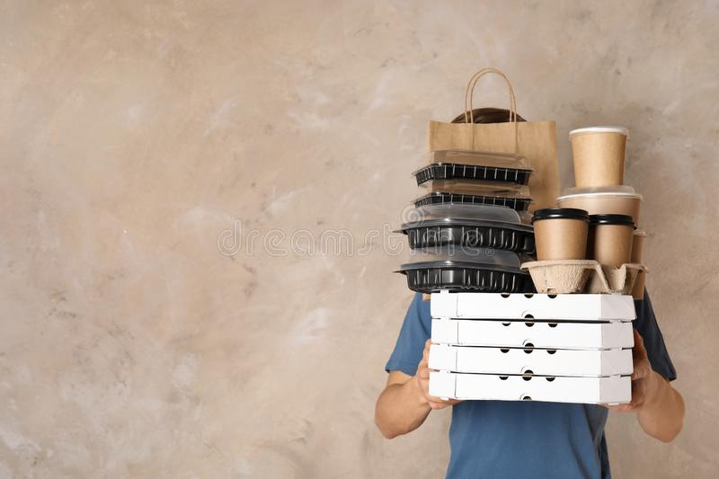 Courier with stack of orders on beige background. Food delivery service. Courier with stack of orders on beige background, space for text. Food delivery service stock photography