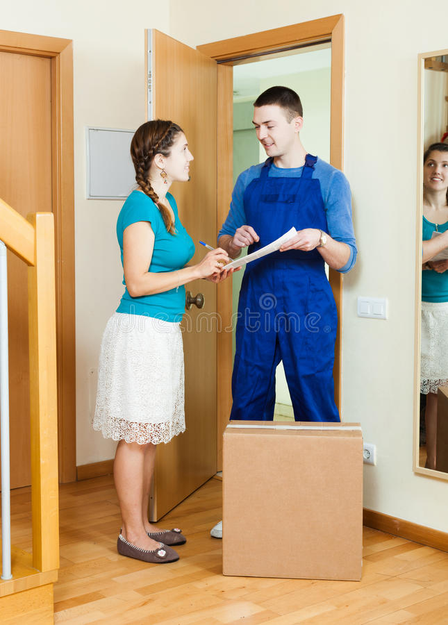 Courier in uniform brought package to housewife. At home royalty free stock photography