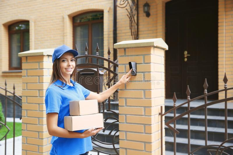 Courier in uniform ringing in doorbell stock images