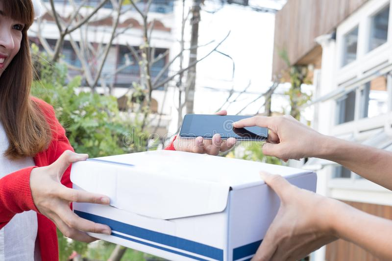 courier wearing santa claus hat delivering a parcel box to customer during christmas holiday. woman confirm delivery by signing o royalty free stock images