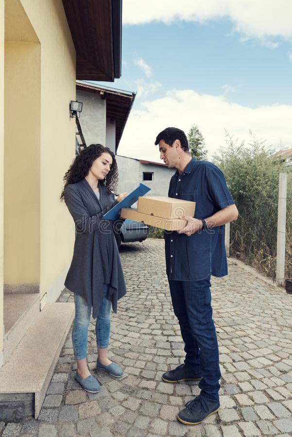 Courier Woman Receiving Boxes Home Delivery. Selective focus royalty free stock photo