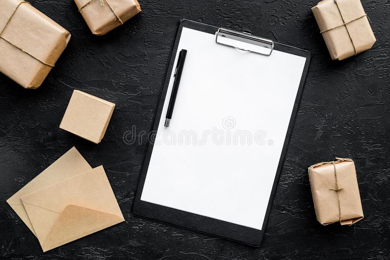 Courier workplace with cardboard box and envelope for delivery on black background top view mockup stock images