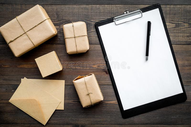 Courier workplace with cardboard box and letters for delivery on wooden background top view mockup stock photography