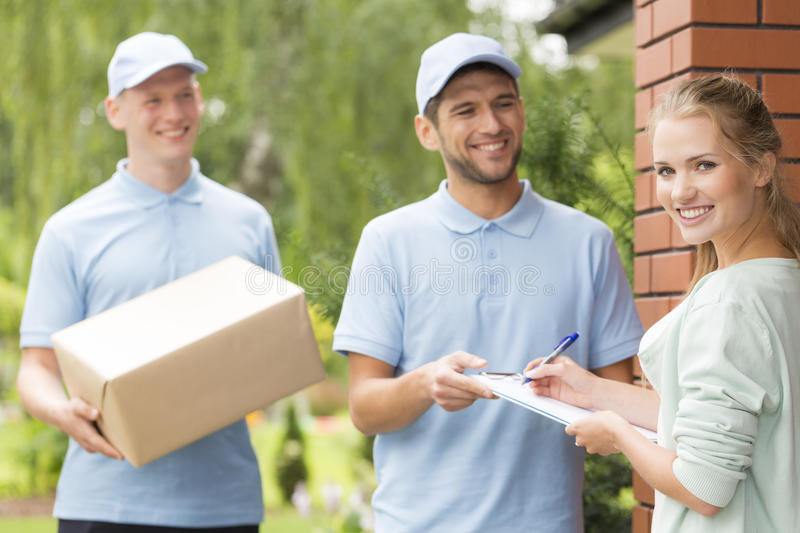Couriers and content woman signing a form stock photos