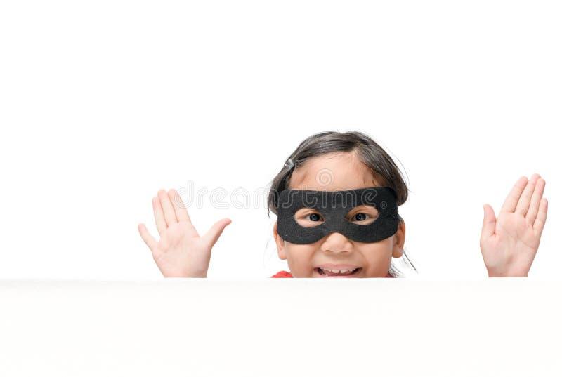 Couro cru da menina do super-herói atrás da placa branca da bandeira isolada fotografia de stock