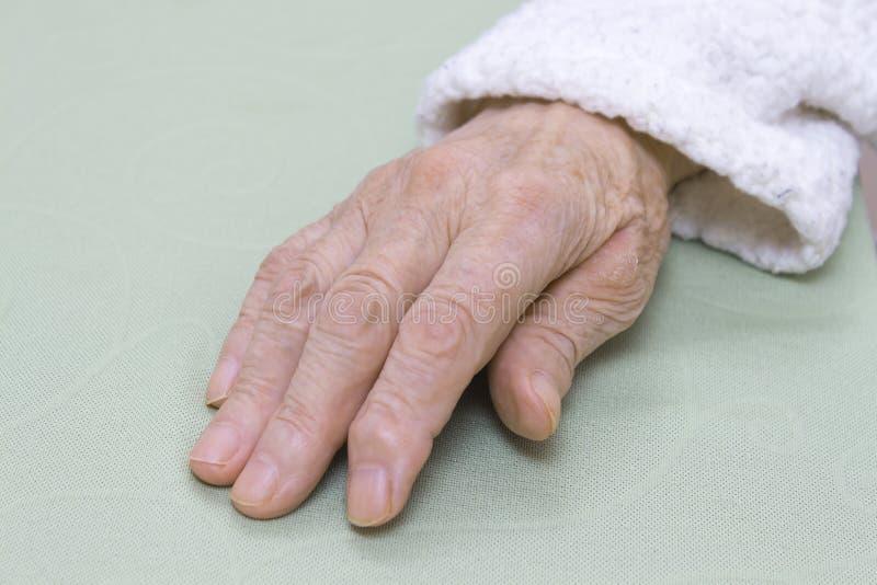 Couro danificado velho da mão de uma mulher adulta mesma em um roupão branco em um fundo claro foto de stock