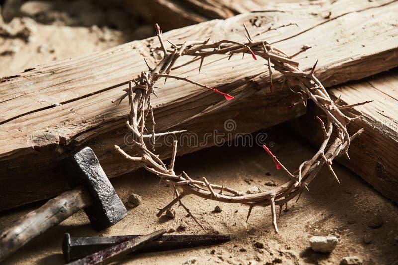 Couronne des épines parmi la croix, marteau avec des clous photographie stock