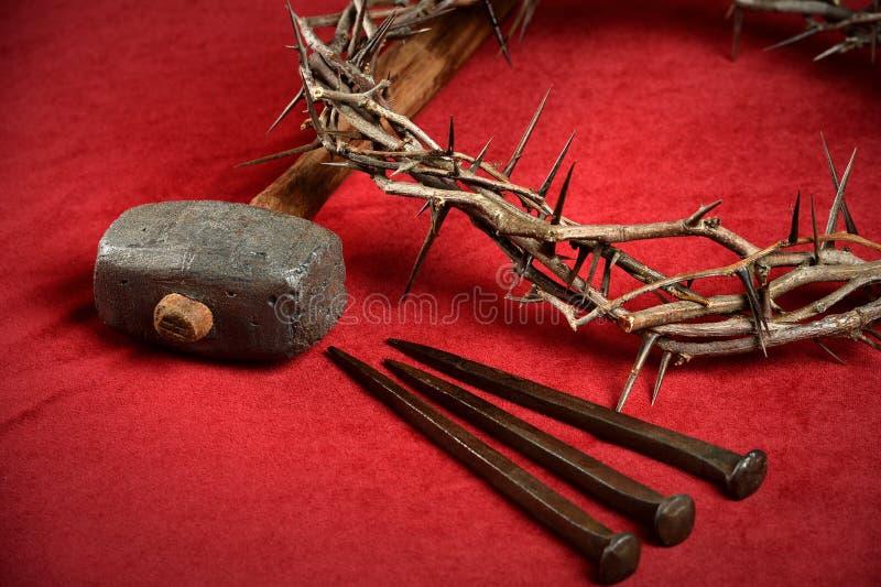 Couronne des clous d'épines et marteau sur le tissu rouge photographie stock