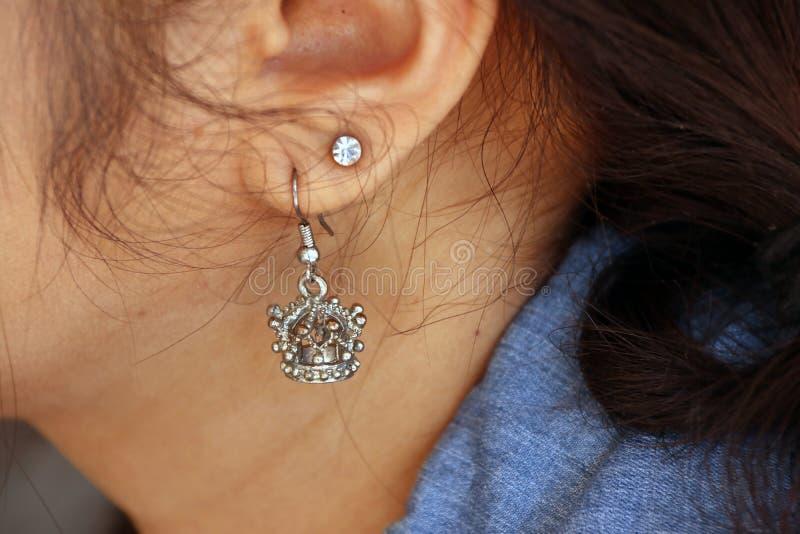 Couronnez la forme de la boucle d'oreille en métal avec la boucle d'oreille de diamant sur l'oreille de photographie stock