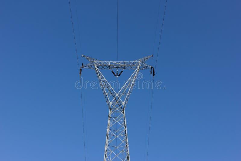 Courrier à haute tension, tour de transport d'énergie contre le ciel bleu image libre de droits