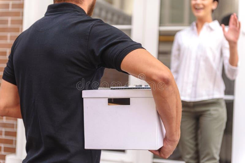 Courrier που παραδίδει ένα κιβώτιο στην ευτυχή γυναίκα στοκ φωτογραφίες με δικαίωμα ελεύθερης χρήσης