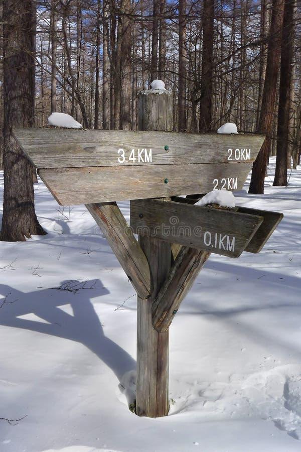 Courrier de signe vide en bois de flèche dans la neige mountian photos stock