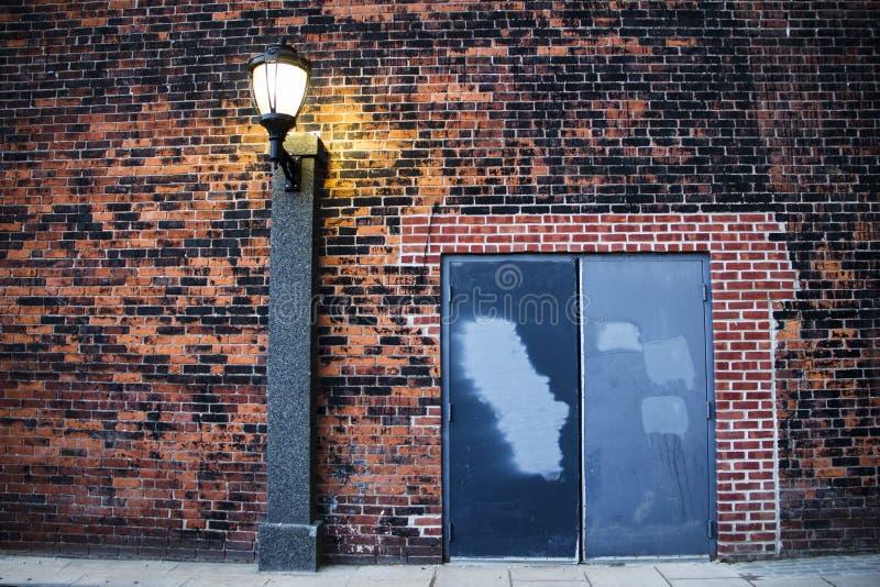 Courrier léger sur un mur de briques près d'une porte images stock