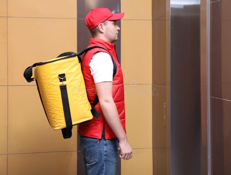Courrier masculin avec sac thermo en attente d'ascenseur Livraison alimentaire images libres de droits