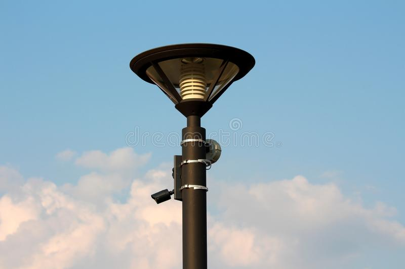 Courrier moderne de réverbère avec la foudre et la vidéo surveillance de LED avec le détecteur de mouvement sur le fond nuageux d photo libre de droits