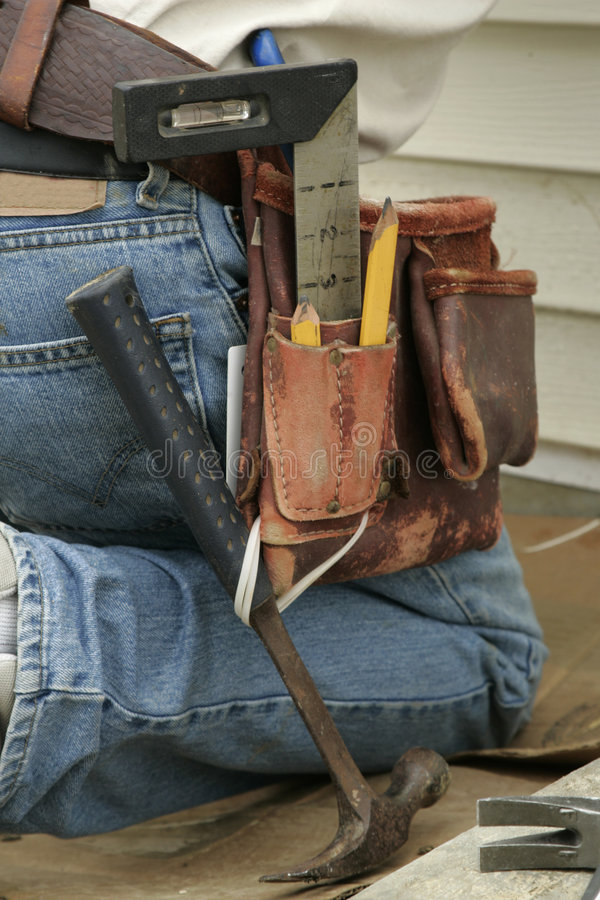 Courroie à genoux d'ouvrier et d'outil photographie stock