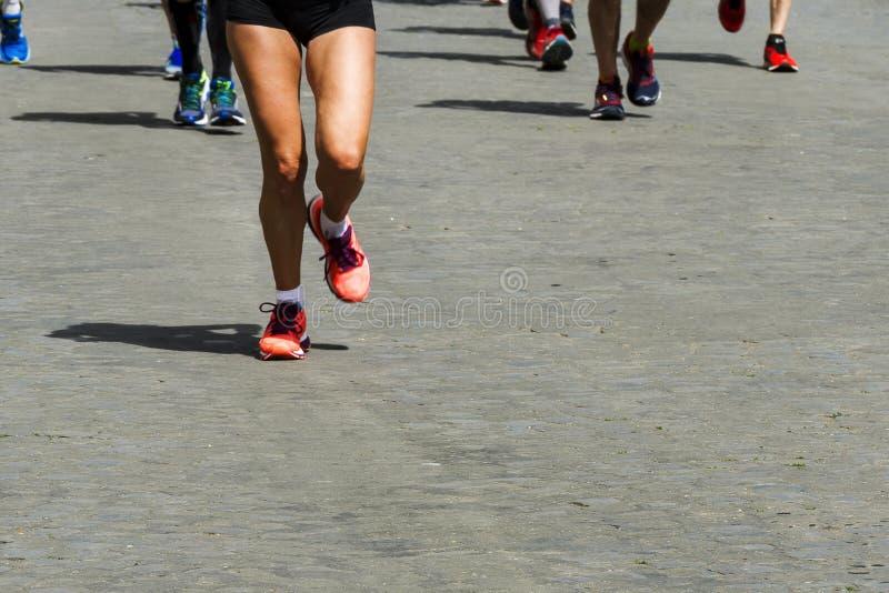 Course courante de marathon, pieds de personnes sur la route urbaine photographie stock libre de droits