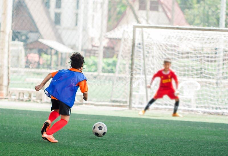 Course de footballeur d'enfant pour tirer la boule au but avec le fond trouble de gardien de but sur le gazon, l'académie artific photos libres de droits