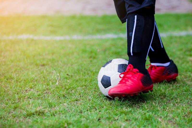 Course de vitesse de footballeur d'enfant pour tirer la boule au but sur l'herbe verte photographie stock