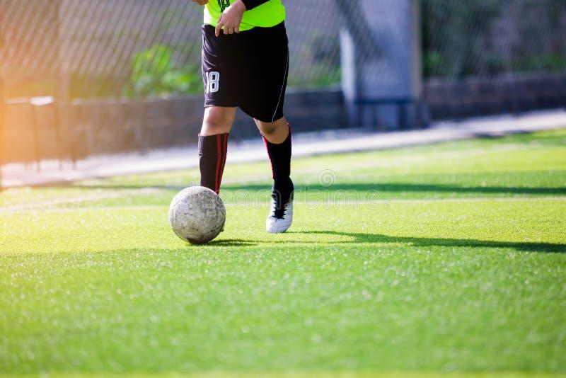 Course de vitesse de footballeur pour tirer la boule au but sur le gazon artificiel photo stock