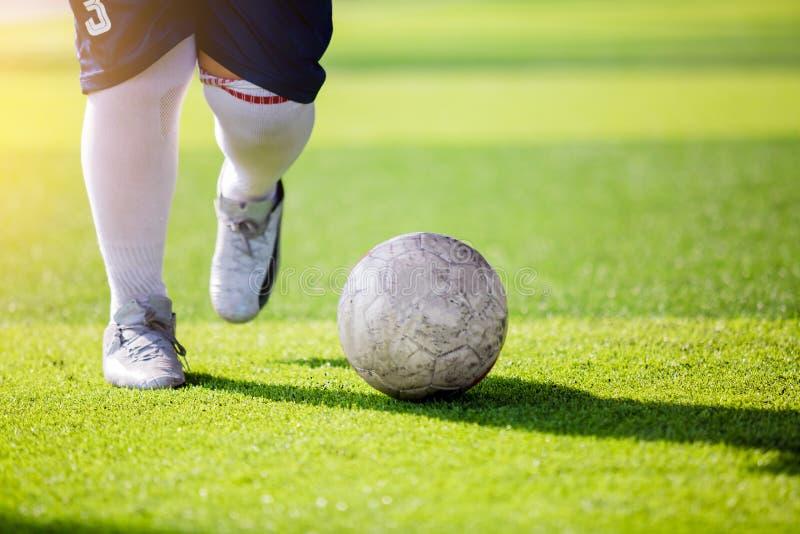 Course de vitesse de footballeur pour tirer la boule au but sur le gazon artificiel image libre de droits