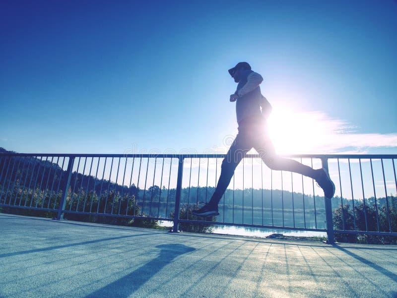 Course sportive d'homme vers le haut du pont Concept de sport et de mode de vie photos libres de droits