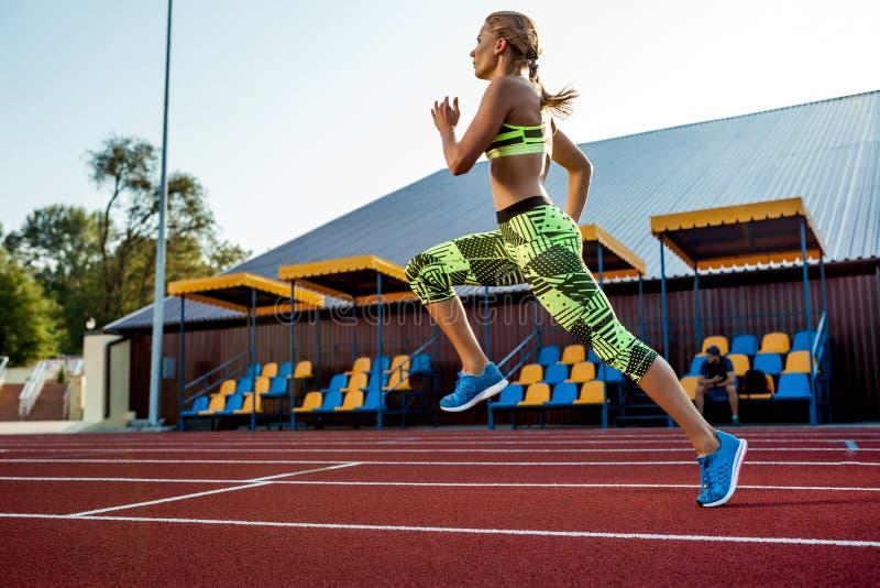 Courses d'un athlète féminin le long du tapis roulant Fond de sport photo stock