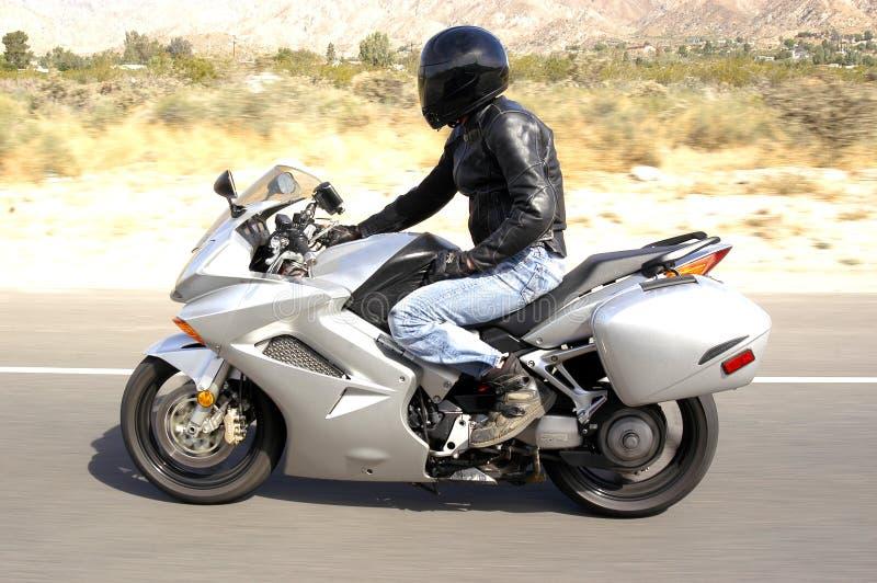 Courses d'un cavalier de moto sur une route dans le Palm Springs de entourage de désert, la Californie photographie stock libre de droits