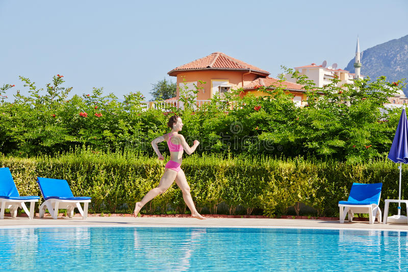 Courses de femme au poolside autour de la piscine photographie stock libre de droits