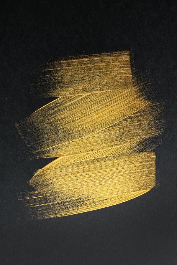 Courses de peinture d'or sur le fond foncé photo stock