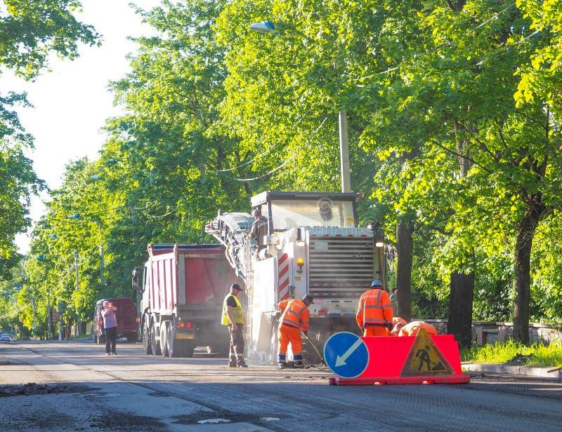 Courses sur route dans la ville Travailler à l'équipement spécial a découpé le vieil asphalte un jour ensoleillé d'été St Petersb image libre de droits