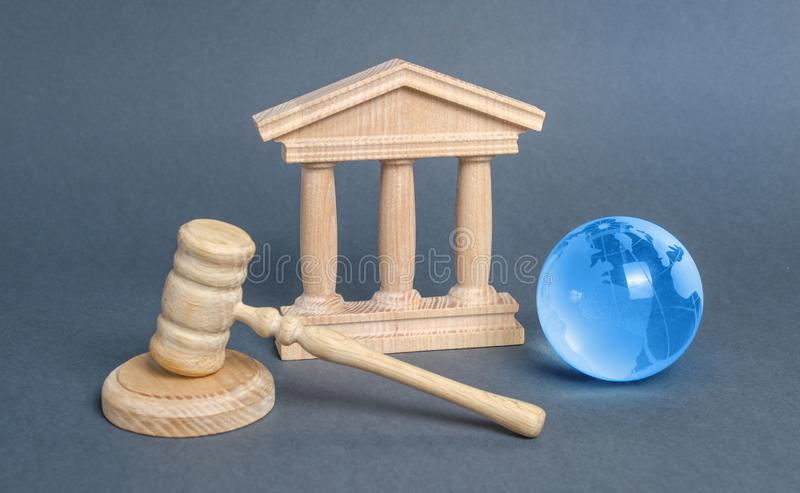 Courthouse, gavel and blue globe planet earth. International Court. Protection of business interests and human rights royalty free stock photography