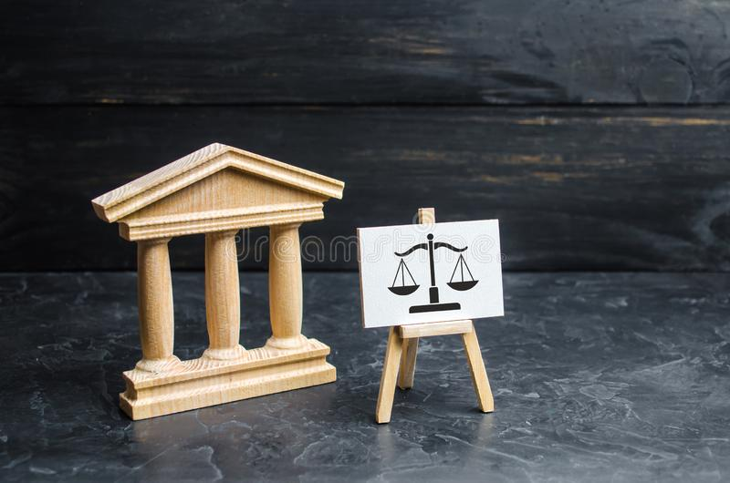 Courthouse and a sign with scales. The concept of the court and the judiciary, justice. Respect for the rights of man and citizen stock photography