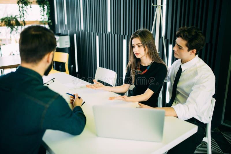 Courtier faisant une présentation à un jeune couple leur montrant un document ce qu'elles regardent avec des expressions sérieuse images stock