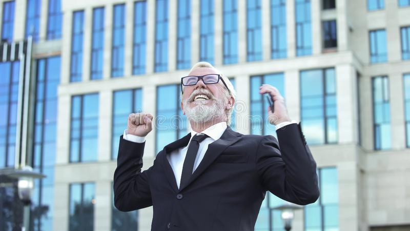 Courtier heureux de marché boursier montrant le téléphone de participation de geste de succès à disposition, encaissant photo stock