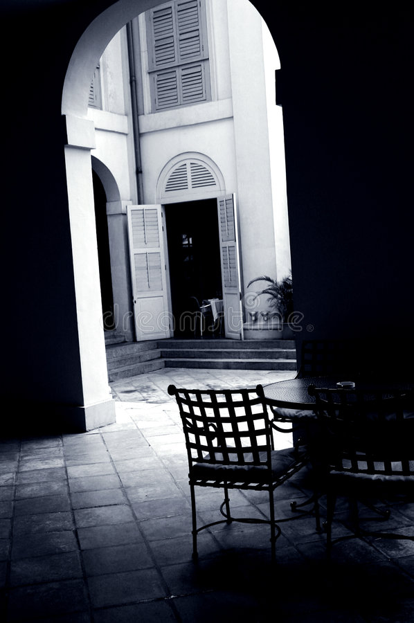 Courtyard Cafe under an arch. A quiet and lonely corner of an outdoors cafe or coffee house in a courtyard, with the tables and chairs placed under an arch which royalty free stock images