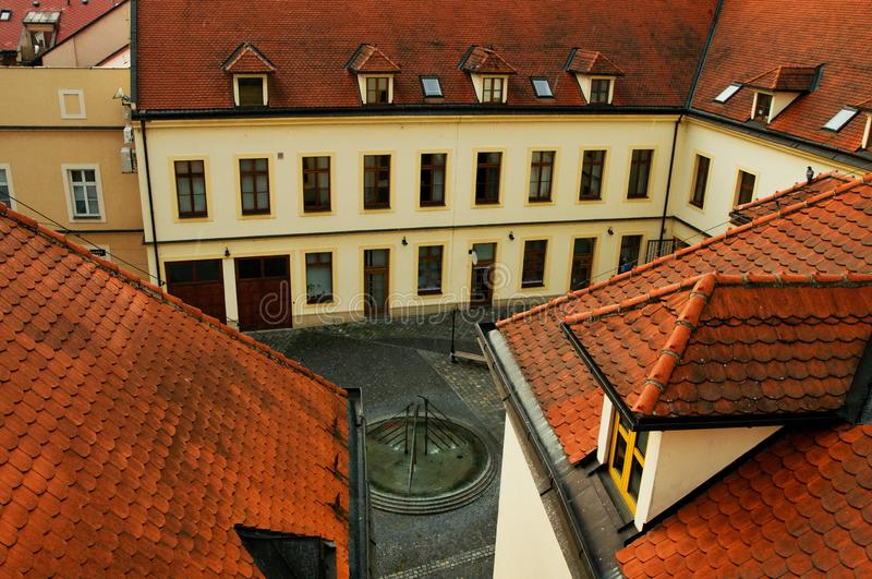 Courtyard with fountain near old town hall, Uherske Hradiste. Small courtyard with fountain , roofs and buildings near the old town hall, evening, in Uherske royalty free stock images